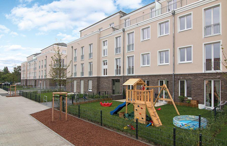 Hofhäuser Karlshorst - Gepflasterter Gehweg und mit Spielzeug bestückter Privatgarten vor den neuen Wohngebäuden