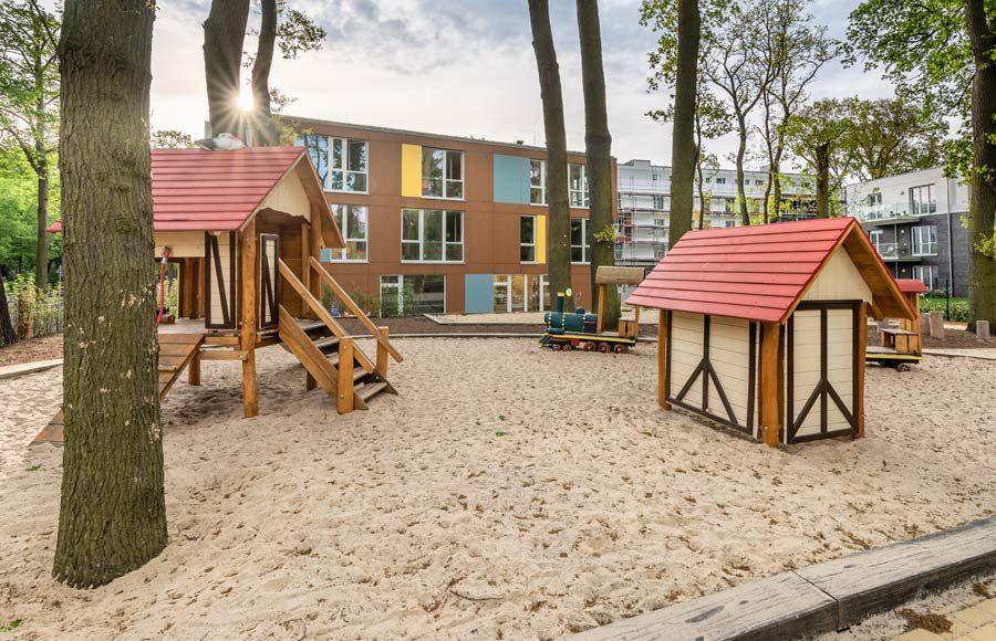 """Kindergarten am Filmpark - Spielplatz der Kita """"Ole Lukoie"""" mit Blick auf das Kita-Gebäude"""