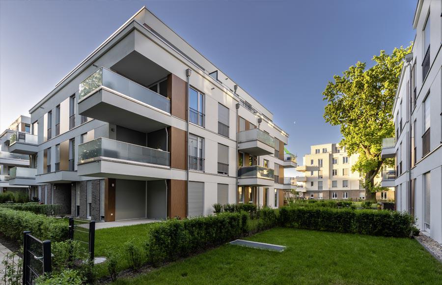 Villen am Filmpark Babelsberg - Ecke einer Stadtvilla mit Blick auf die großen Balkonen in den Obergeschlossen, die Terrasse im EG und dem grünen Rasen davor vor blauem Himmel