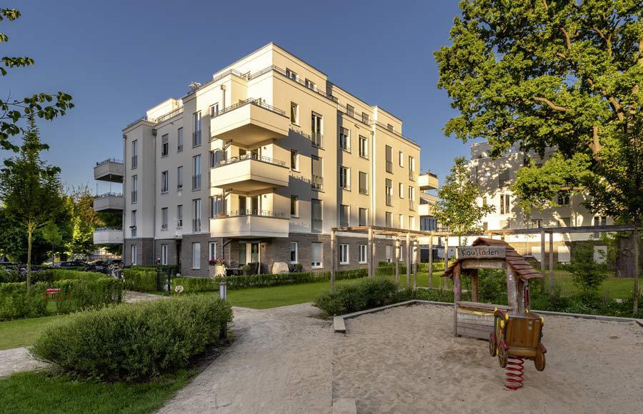 Villen am Filmpark Babelsberg - Blick eine Stadtvilla, davor mit grünen Freiflächen, Gärten und Kinderspielplatz, bei Sonnenaufgang
