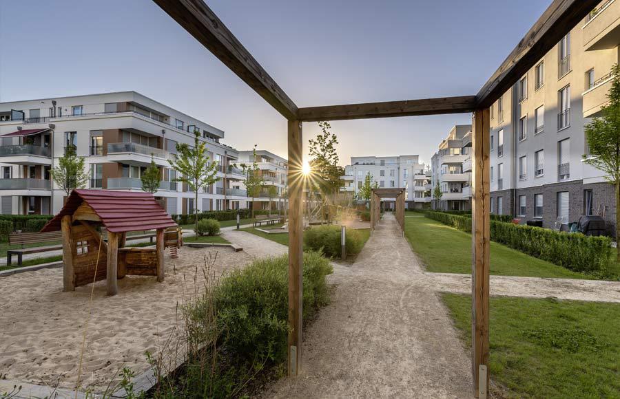 Villen am Filmpark Babelsberg - Blick in den gestalteten Hof zwischen den Stadtvillen mit grünen Freiflächen, Gärten und Kinderspielplatz bei Sonnenaufgang
