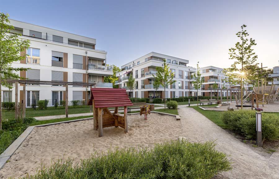 Villen am Filmpark Babelsberg - Blick in den gestalteten Hof zwischen den Stadtvillen mit grünen Freiflächen und Kinderspielplatz bei Sonnenaufgang