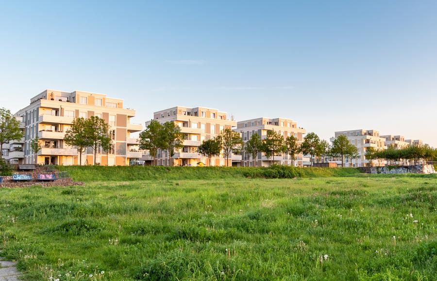 Wohnen an den Gärten der Welt - Blick von grüner Wiese auf die Stadtvillen bei Sonnenaufgang