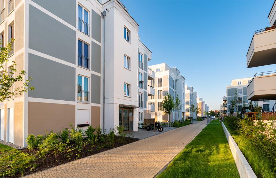 Wohnen an den Gärten der Welt - Blick auf Eingangsbereich einer Stadtvilla mit Briefkästen, Fahrradstellplätzen und grünem Rasen