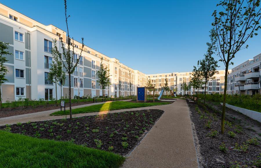 Wohnen an den Gärten der Welt - Innenhof mit Spielplatz und neu angepflanzten Grünflächen