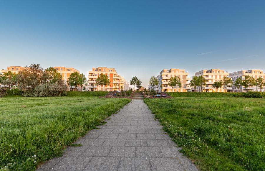 Wohnen an den Gärten der Welt - Blick aus dem Park auf 6 Stadtvillen bei Sonnenaufgang