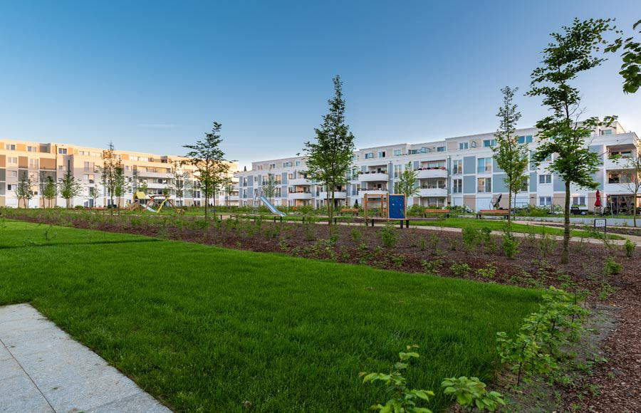 Wohnen an den Gärten der Welt - grüner Innenhof mit Spielplatz und Riegelbebauung im Hintergrund