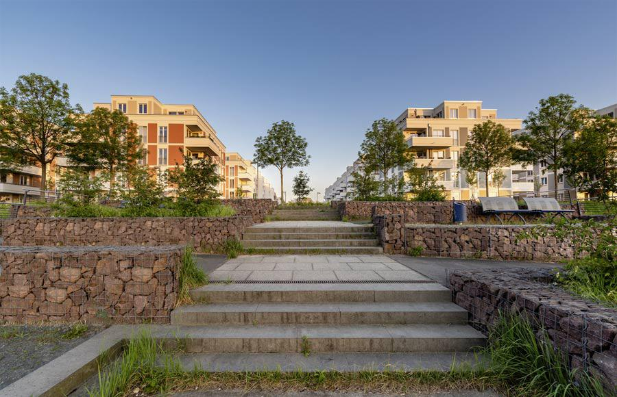 Wohnen an den Gärten der Welt - Blick aus dem Park auf die Stadtvillen bei Sonnenaufgang