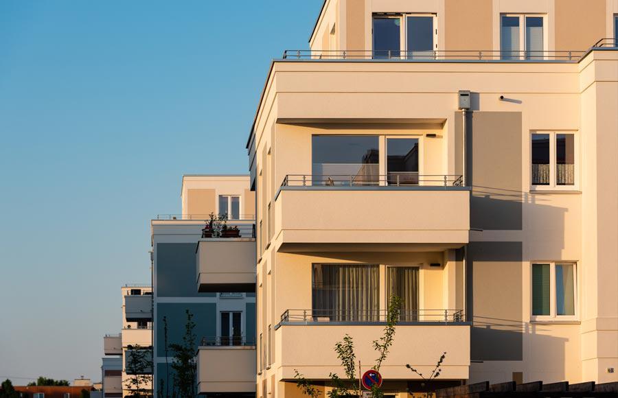 Wohnen an den Gärten der Welt - Ecke einer Stadtvilla mit Balkonen bei Sonnenaufgang und blauem Himmel