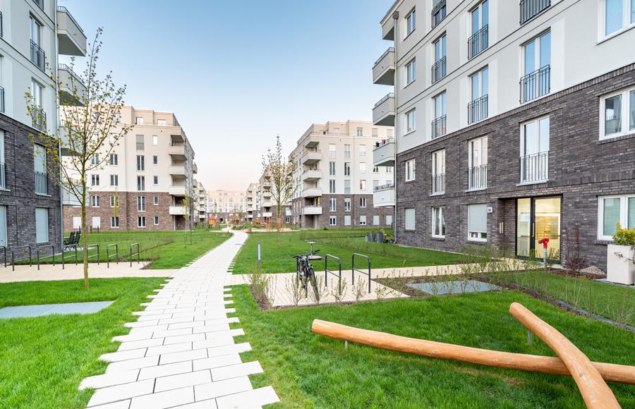 BrunnenViertel - Liebevoll gestalteter Innenhof zwischen den Stadtvillen mit grünen Rasenflächen, Spielflächen und Fahrradstellplätzen