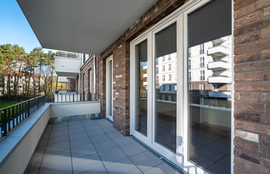 BrunnenViertel - Balkon vor Fensterfront mit großen Kiefern im Hintergrund