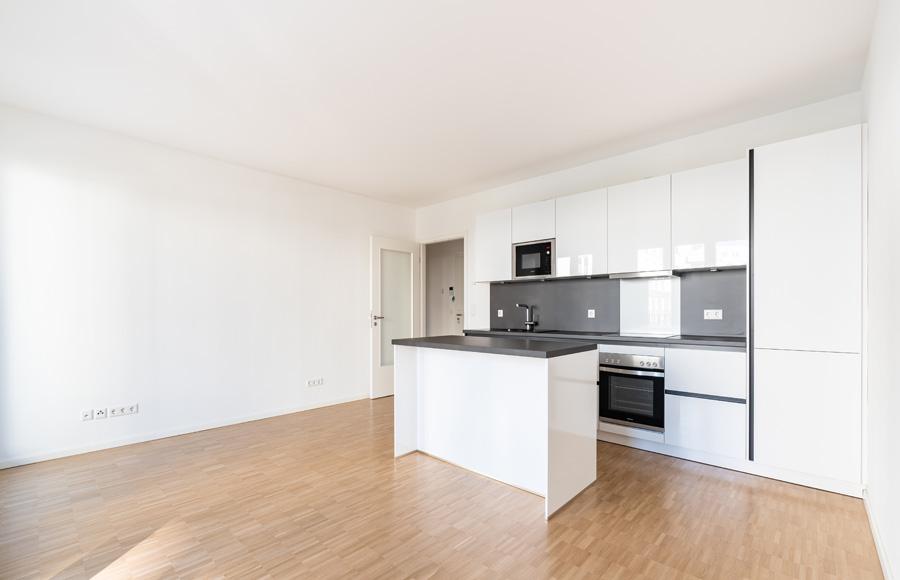 BrunnenViertel - Wohnküche mit hochwertigem Parkett, Küchenzeile und modernem Küchenblock in weiß und grau