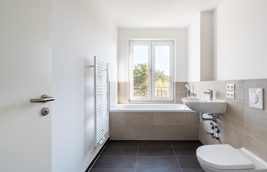 BrunnenViertel - Hochwertiges Bad im Neubau mit modernem Feinsteinzeug, qualitativen Armaturen und Badewanne vor einem Fenster mit Ausblick ins Grüne