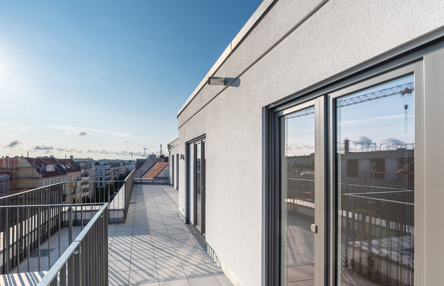 Rigaer Straße - Blick entlang Dachterrasse und auf dahinterliegende Stadt bei blauem Himmel