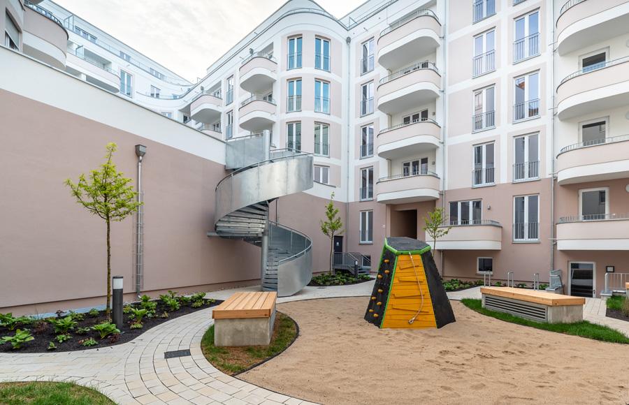 Rigaer Straße - Innenhof mit Spielplatz im Vorder- und neuem sechsgeschossigem Wohngebäude im Hintergrund