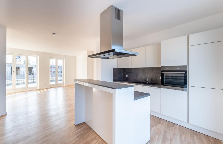 Rigaer Straße - Innenansicht helles Wohnzimmer und moderne Wohnküche mit doppelter Küchenzeile, Parkett und bodentiefen Fenstern