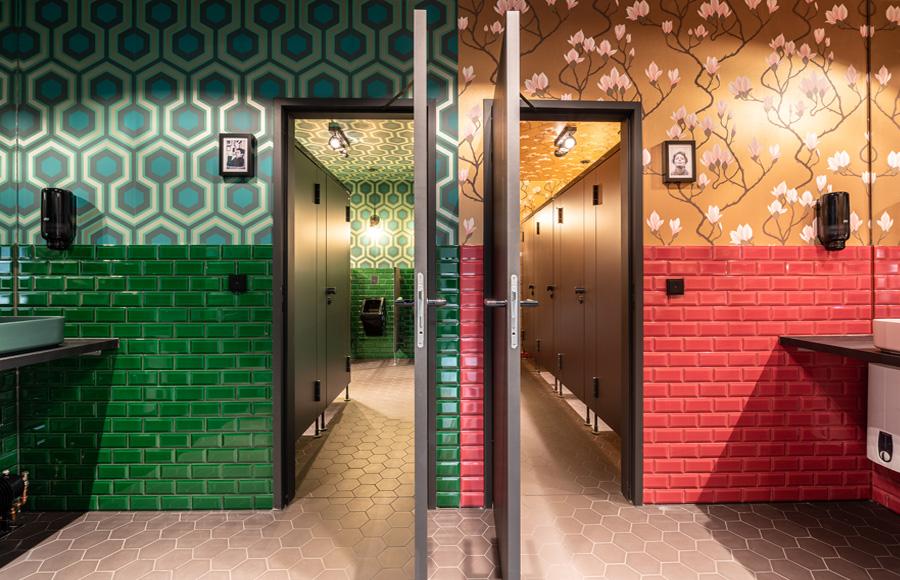 Studio Five - Blick in WC-Bereiche Damen rechts und Herren links mit unterschiedlicher farblicher und grafischer Gestaltung