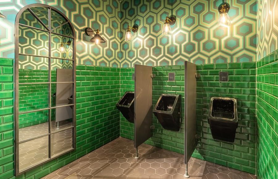 Studio Five - Blick in WC-Bereich Herren mit hohen Spiegeln, grünen Fliesen, grafischer Tapete in Grüntönen und modernen Lampen im Retro-Stil