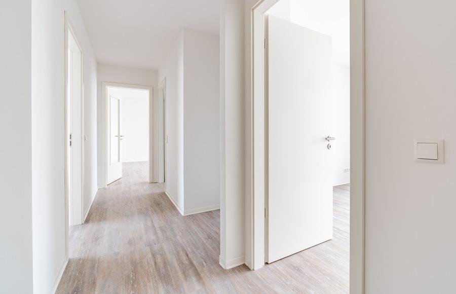 Zossener Straße -Innenansicht Flur mit abgehenden Zimmern, lichtdurchflutet, helles Parkett, weiße Wände und Türen
