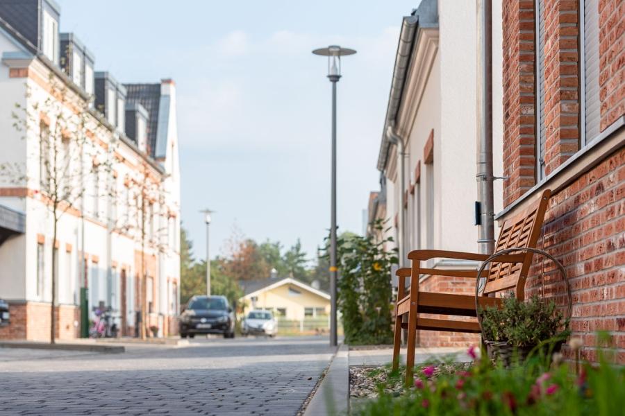 Grüne Aue Biesdorf Froschperspektive auf Anwohnerstraße, Klinkerfassade vorn rechts mit Holzbank davor, im Hintergrund unscharf Variante Fassade mit Klinker-Putz-Fassade und Dachgiebel