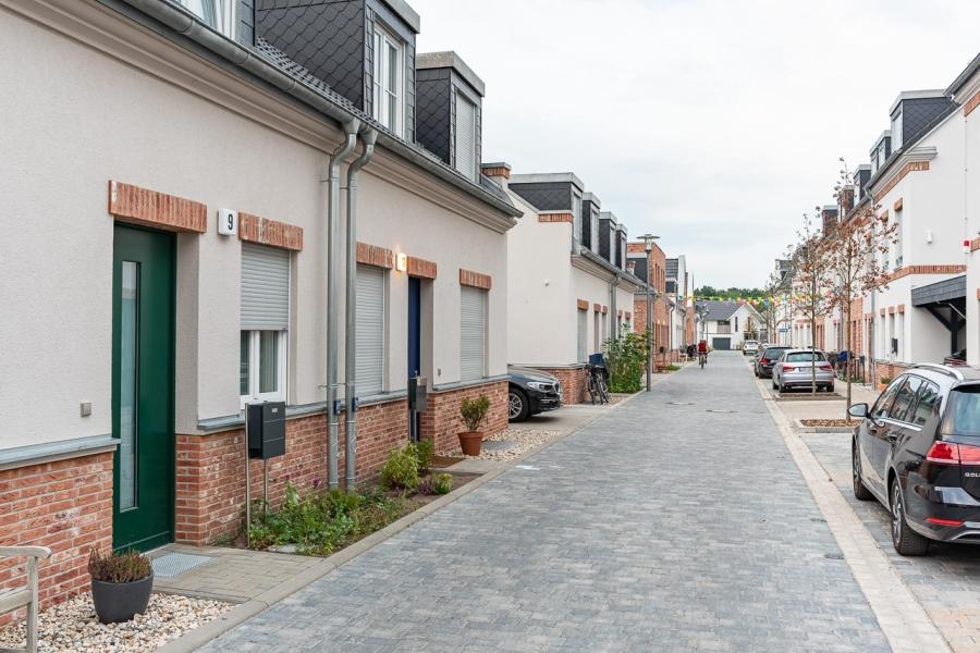 Grüne Aue Biesdorf Kleine gepflasterte Anwohnerstraße mit verschiedenfarbigen Hauseingangstüren an Doppelhäusern