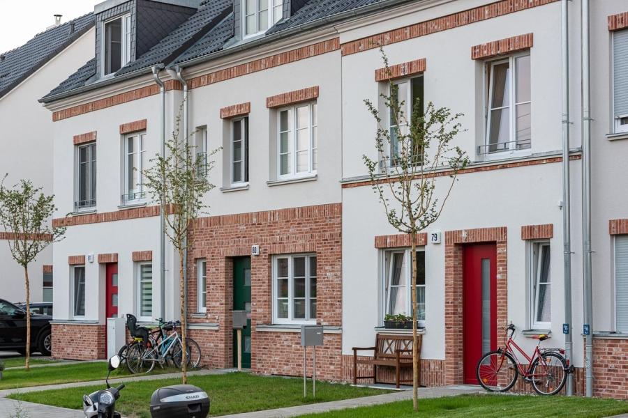 Grüne Aue Biesdorf Blick auf Fassaden dreier Reihenhäuser mit unterschiedlicher Fassadengestaltung. Außen rote Eingangtüren, in der Mitte eine grüne.