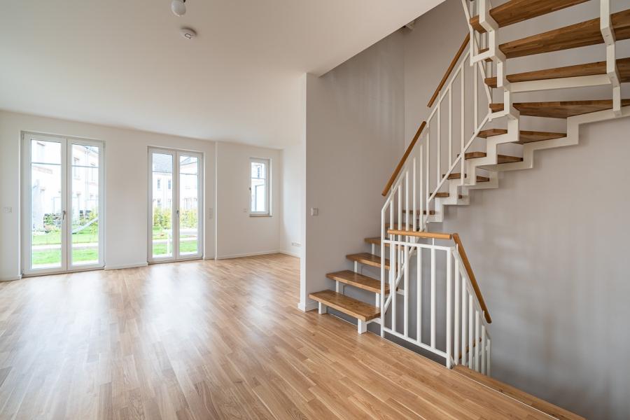 Grüne Aue Biesdorf Innenansicht Wohnzimmer mit Treppe zu Keller und Obergeschoss. Hochwertiger Parkettboden, 2 Terrassentüren, lichtdurchfluteter großzügiger Raum.