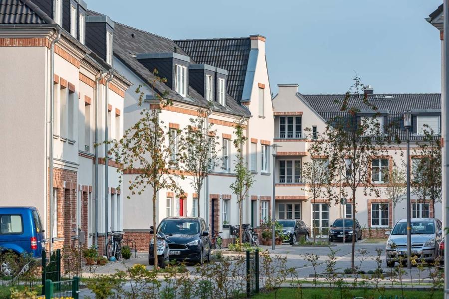 Grüne Aue Biesdorf Impression aus Wohngebiet mit Blick auf Reihen- und Mehrfamilienhäuser, parkende Autos davor